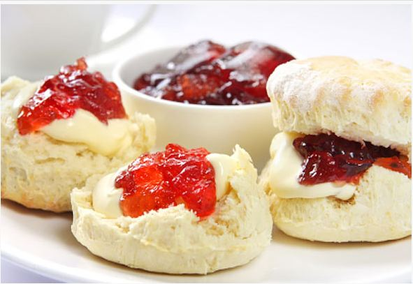 Pot of tea with scone, clotted cream and jam